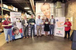 Pilgrim's and Kroger team members in front of donation items to Hurricane Relief