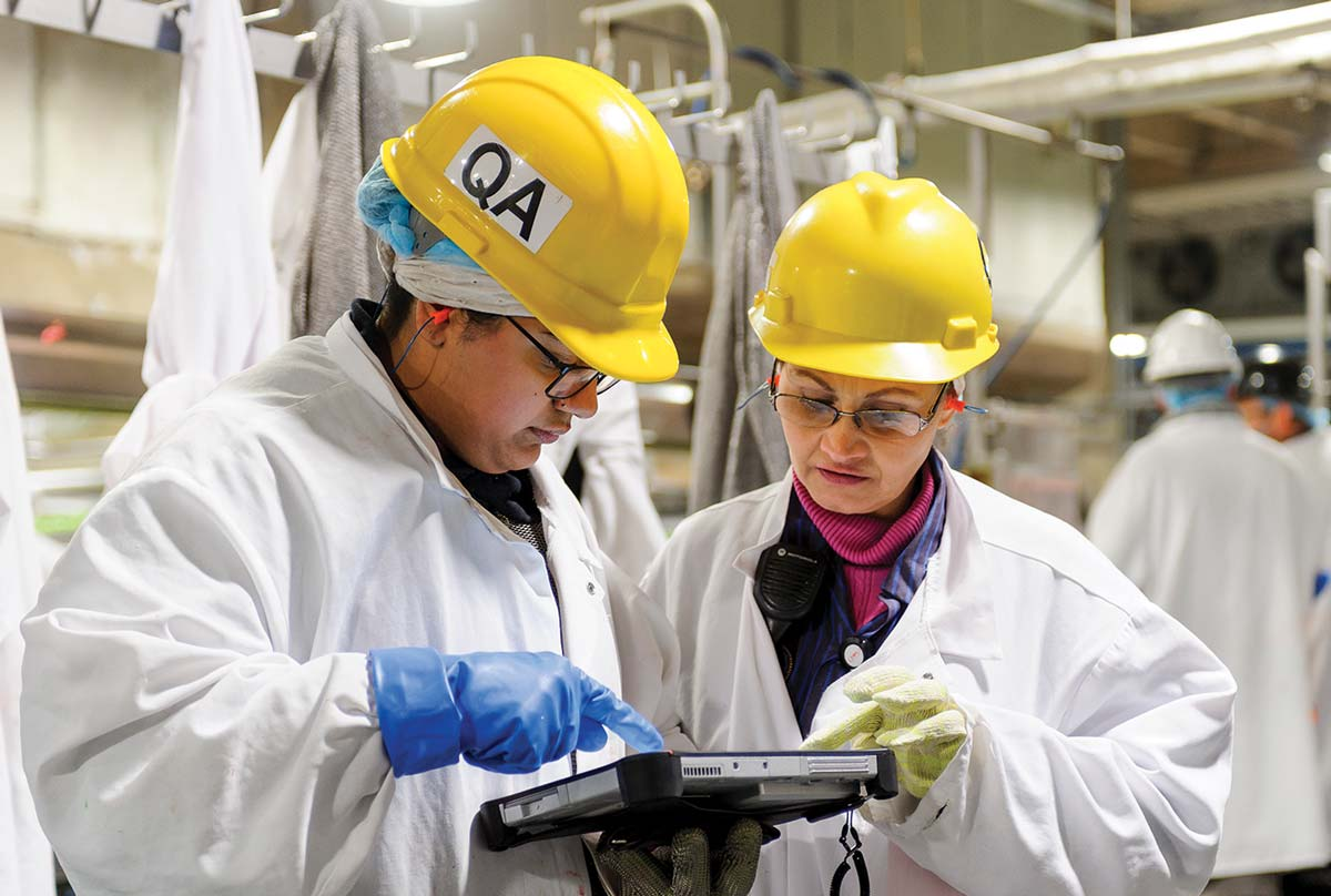 Two manufactures in protective gear looking at an ipad.